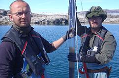 Nicolaj Larsen og Kurt Kjær ved Sydøstgrønland med en nyoptaget kerne. Man kan se overfladen af søens bund og overgangen til vandet. Foto: Anders Bjørk